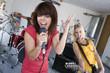 Three teenagers (15-17) in garage band, teenage girl singing in foreground