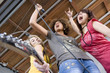 Three teenagers (15-17) singing and playing guitar in band, low angle view