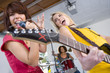 Three teenagers (15-17) in garage band, teenage girls singing and playing guitar in foreground