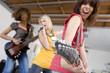 Three teenage girls (15-17) in garage band, teenage girl playing electric guitar in foreground