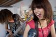 Three teenage girls (15-17) in garage band, teenage girl singing in foreground