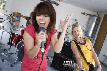 Three teenagers (15-17) in garage band, teenage girl singing in foreground
