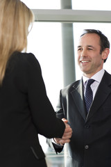 Businessman shaking hands with female client or colleague