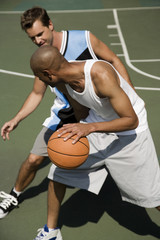 Two men playing basketball on a green urban outside court