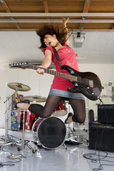 Teenage girl (15-17) playing electric guitar in garage, jumping in air