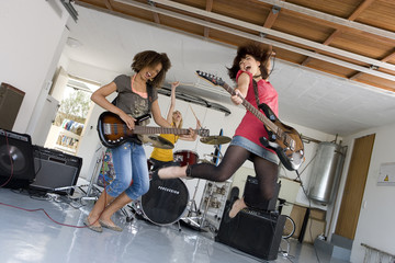 Three teenagers (15-17) playing electric guitars and drums in garage band
