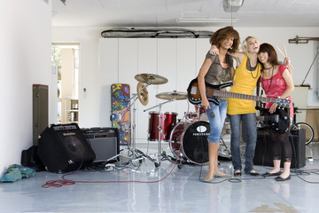Three teenage girls (15-17) in garage band, smiling, portrait