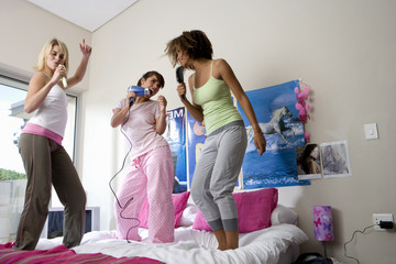 Three teenage girls (15-17) standing on bed, singing, low angle view