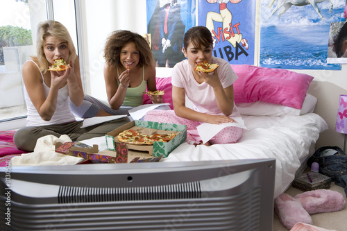 Three teenage girls (15-17) sitting on bed eating pizza, portrait