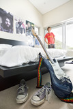 Electric guitar and shoes in bedroom, close-up