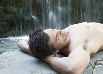 A man relaxing by a waterfall