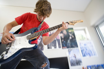 Teenage boy (16-18) playing electric guitar in bedroom, low angle view