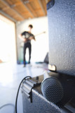 Teenage boy (16-18) playing electric guitar in garage, focus on microphone in foreground