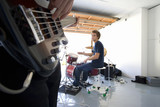 Teenage boy (16-18) playing drums in garage, looking at friend playing electric guitar in foreground