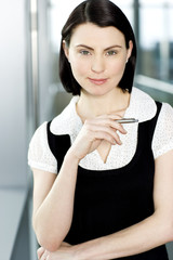 Portrait of young businesswoman or secretary holding a pen
