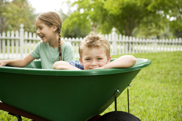 two children sitting in a wheelbarrow