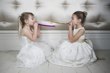 Two little girls wearing party dresses blowing party blowers