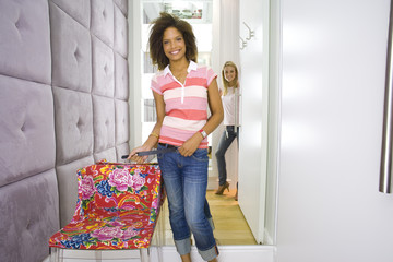 Two young women standing in corridor by change rooms of shop, smiling, portrait