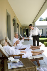 Waiter standing by mature couple sitting on deck chairs wearing white bath robes