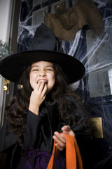 Girl in a witch's costume at a Hallowe'en party, eating sweets