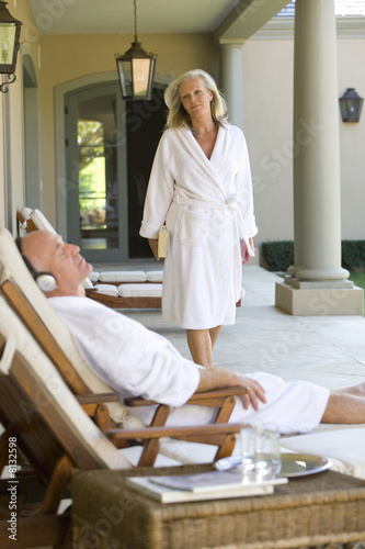 Mature couple wearing white bath robes, woman looking at man wearing headphones lying in deck chair