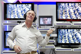 Mature man shopping in television store, 'playing' air guitar by screens