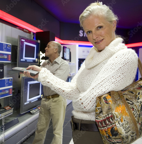 Mature couple shopping in television store, portrait of woman smiling in foreground
