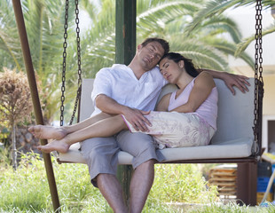 A couple relaxing on a swing