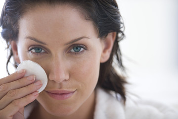 Young woman cleaning face with tissue pad, portrait, close-up