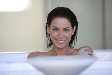 Young woman in bath, smiling, portrait