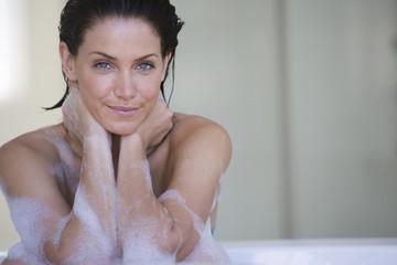 Young woman in bubble bath, smiling, portrait