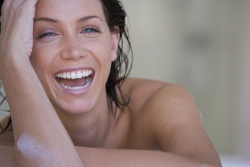 Young woman in bubble bath, laughing, portrait, close-up