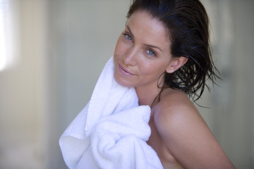 Young woman drying herself with white towel, smiling, portrait