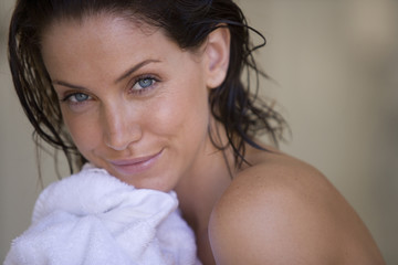 Young woman drying herself with white towel, smiling, portrait, close-up