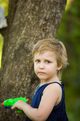 Little girl plays near a tree