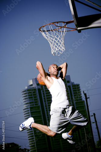 Young  African American man jumping with a basketball on an urban basketball court