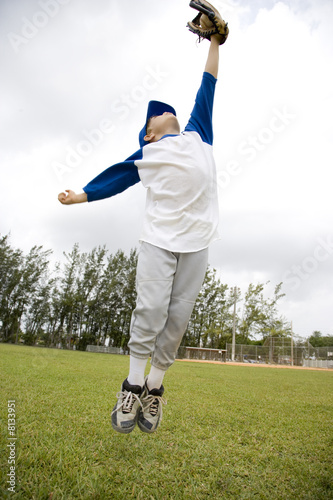 Boy jumping to catch baseball
