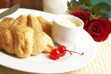 Croissant breakfast with glaze cherries