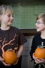 Two children holding orange Hallowe'en pumpkins