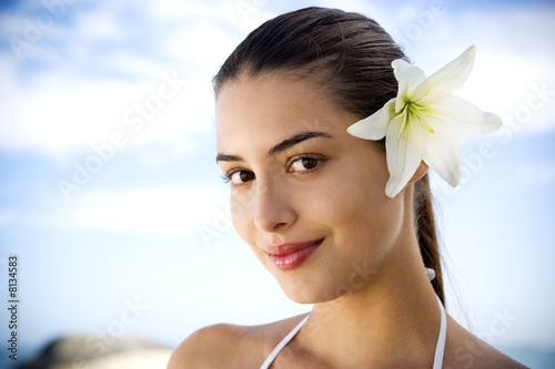Portrait young Hispanic woman with flower in hair