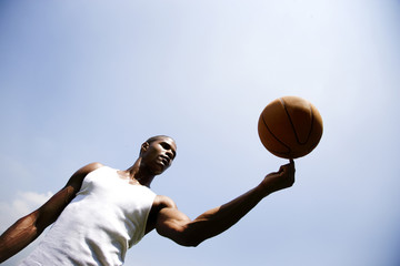 Young African American man spinning a basketball on his finger
