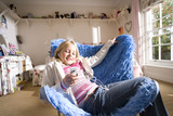 Girl (8-10) sitting in blue shag pile chair listening to MP3 player, smiling