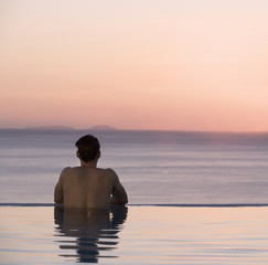 A man in a pool watching the sunset