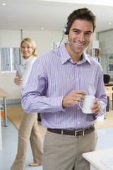 Businessman wearing headset holding mug, woman in background, smiling, portrait