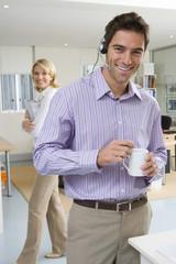 Businessman wearing headset holding mug, woman in background, smiling, portrait