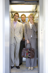 Small group of people in lift, businessman making face at businesswoman with hand to face