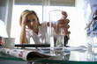 Young businesswoman at desk holding glass with soluble tablet, head in hand, focus on glass (differential focus)