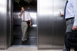 Businessman on mobile phone in lift, colleague pressing button by lift in foreground, mid section