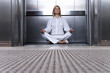 Businesswoman meditating in elevator, ground view