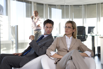 Businessman and woman in armchairs in office, man glaring over shoulder at woman